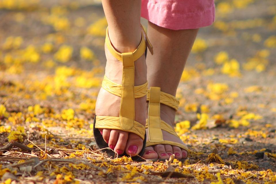 Pies hermosos con sandalias amarillas